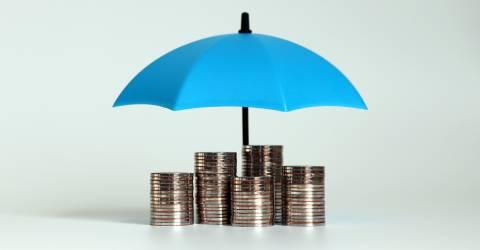 Een stapel van munten met een open blauwe paraplu.